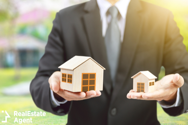 businessman holding small and big house