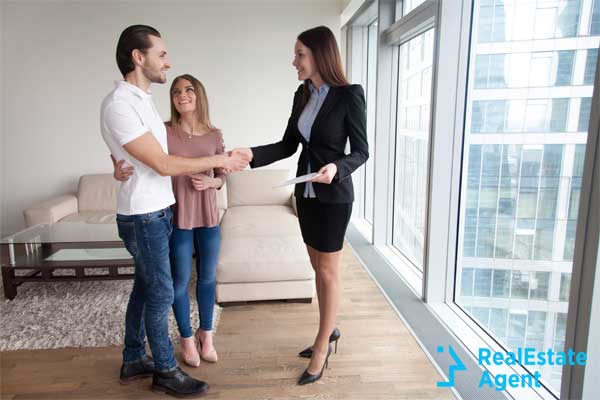 Friendly realtor shacking hand of happy couple