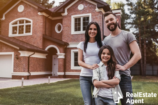 happy family standing near modern house