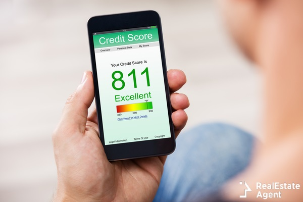 man holding a smartphone showing a good credit score