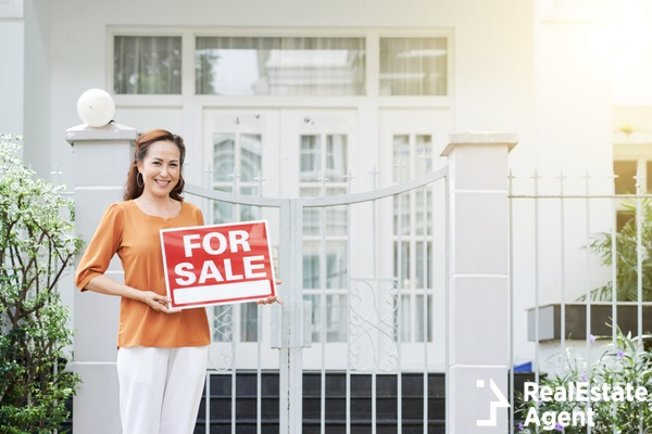 mature woman holding a sale sign