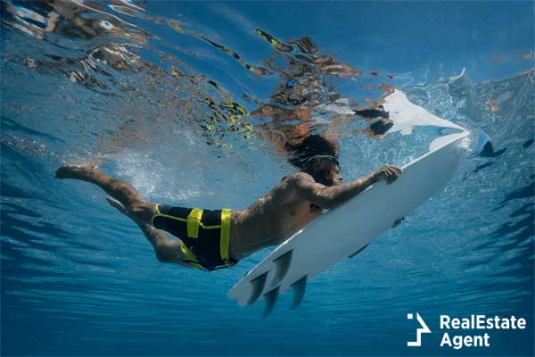 Surfer with surf board dive underwater