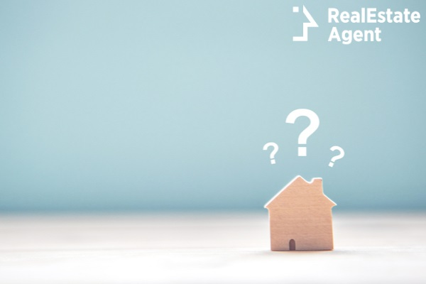 wooden house model with questions sign